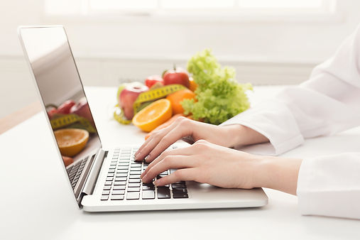 A person using a MacBook Pro on a white table with garden fresh fruits like apples, grapes and oranges