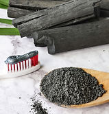 Charcoal toothpaste on a red and white toothbrush next to finely powdered charcoal on a wooden spoon and heap of charcoal sticks