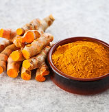 Freshly ground turmeric powder in a round ceramic bowl next to a stack of turmeric fingers