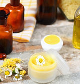 Soothing paw and snout butter by Doggiliciouus in a white bottle next to flowers and jars containing various essential oils