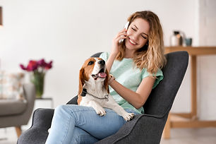 Woman sitting in a grey chair in a living room with a couch, vase with flowers and table with coffee pot in the background. A beagle sits smiling on her lap as she talks on the phone