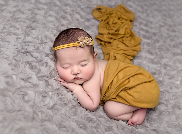 Newborn baby girl posed on grey background with mustard yellow accents