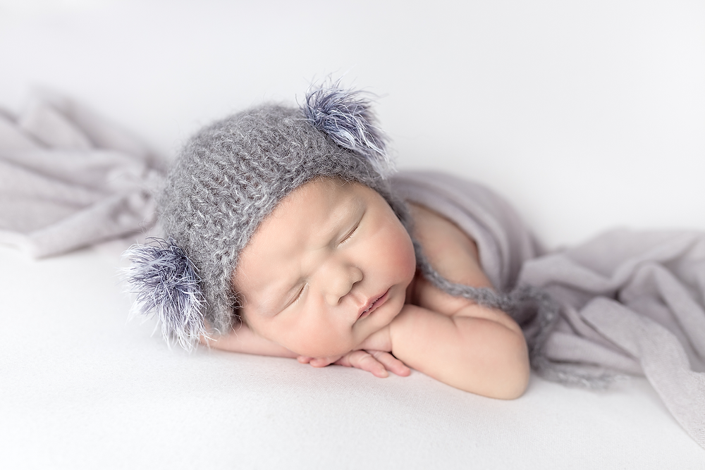 Newborn baby posed in head on hands with grey wrap and hat