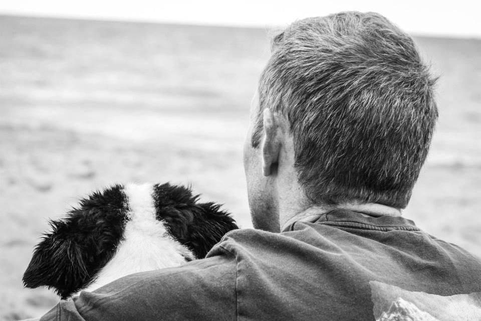 black and white image of a dog and his owner
