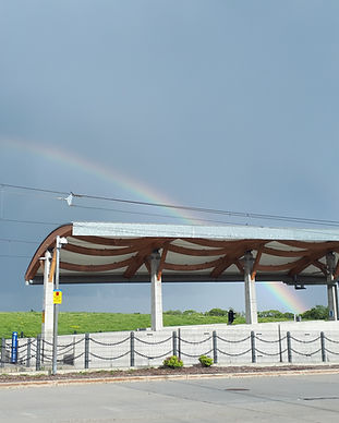 An LRT station with a rainbow visible in the background.