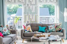 Cala-Homes-grey-sofa-bright-cushions-geometric-wallpaper-showhome-photography