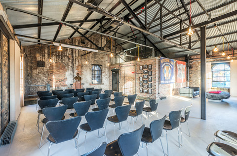 interior photography of refurbished space with exposed brickework and steel framed roof