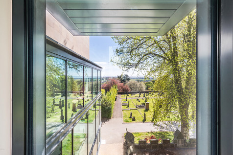 view from inside art gallery to graveyard beyond
