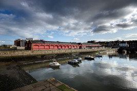 exterior architectural photography of Newhaven Harbour and fish market with clouds and reflections