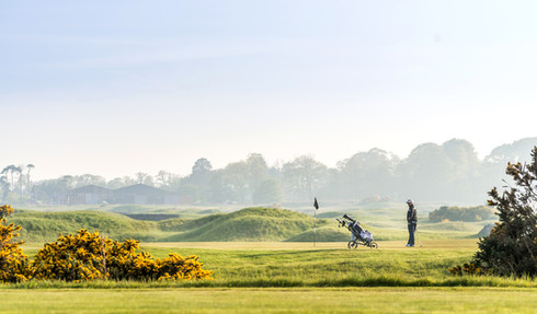 lifestyle photography of golfer on golf course in early morning mist