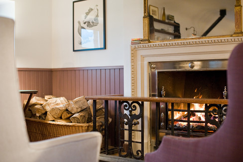 lifestyle detail photography of cosy fireplace with armchairs in period cottage