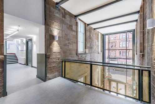 interior photography of bridge link between brick double height entrance foyer