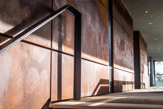 exterior detail photography of corten steel cladding along external terrace