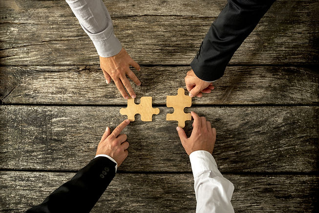 Four Successful Business Men Joining Two Puzzle Pieces Each Being Held By Two Partners.jpg