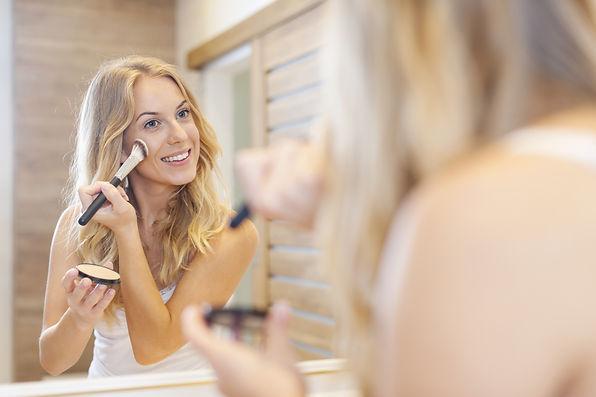 Blonde beautiful woman doing makeup in f