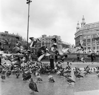 Gilr feeding pidgens in Plaça de Catalu