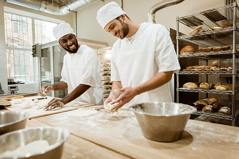 happy bakers kneading dough together at baking manufacture and talking.jpg