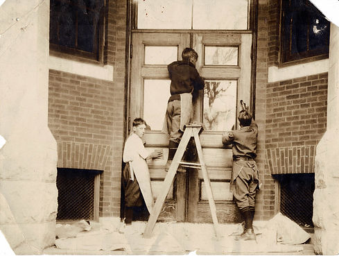 early 1900s photo of three boys sanding the main door at Center School