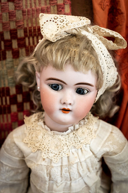 Antique doll with blonde hair, porcelain head, wooden body and white lace dress