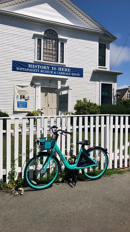 Photo of a teal bike leaning on a white picket fence in front of the Mattapoisett Museum