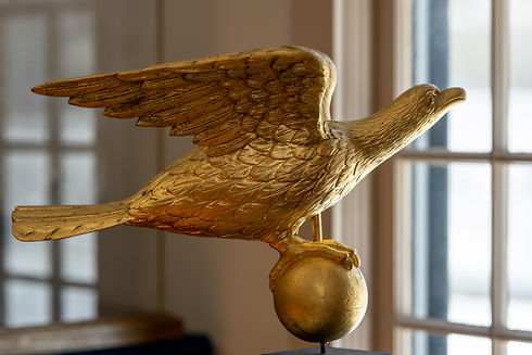 Sculpture of an eagle perched on top of a gold ball