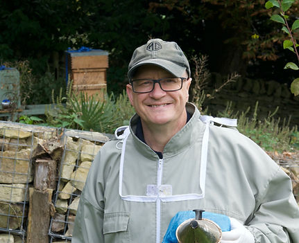Harry of Harry's Honey standing by hives with a smoker