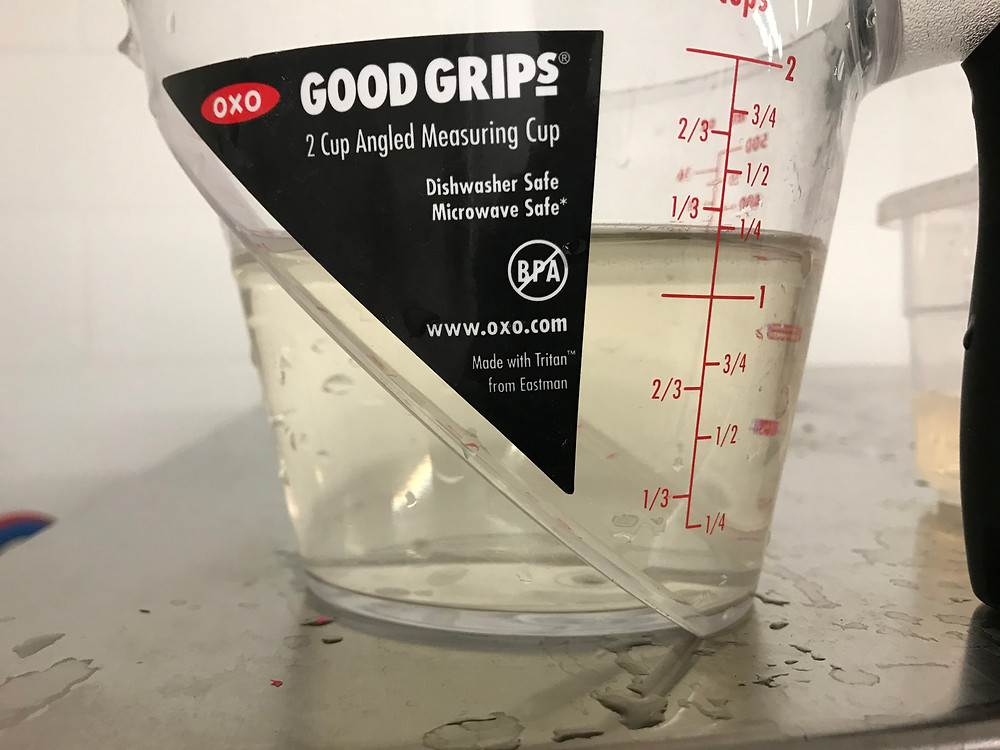 Image of water in a measuring cup that has some cloudiness