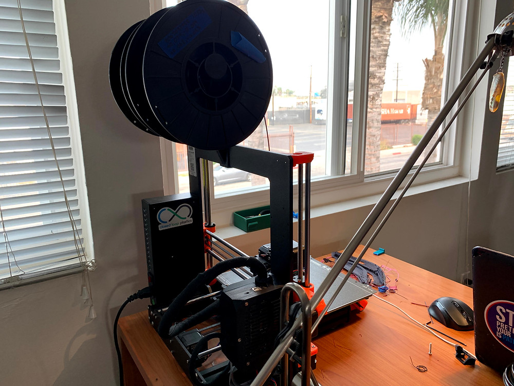 Desktop 3D printer printing next to an opened window