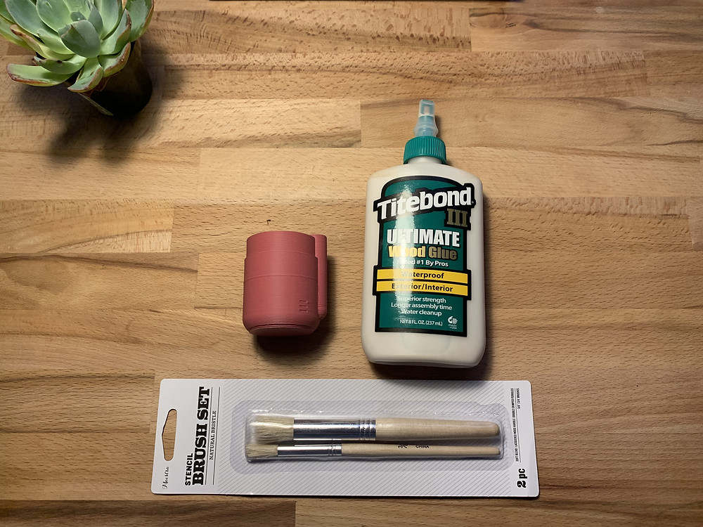 A succulent is in the top corner, the planter reservoir is to the left of the Titebond III wood glue, and the set of small paintbrushes is at the bottom of the image