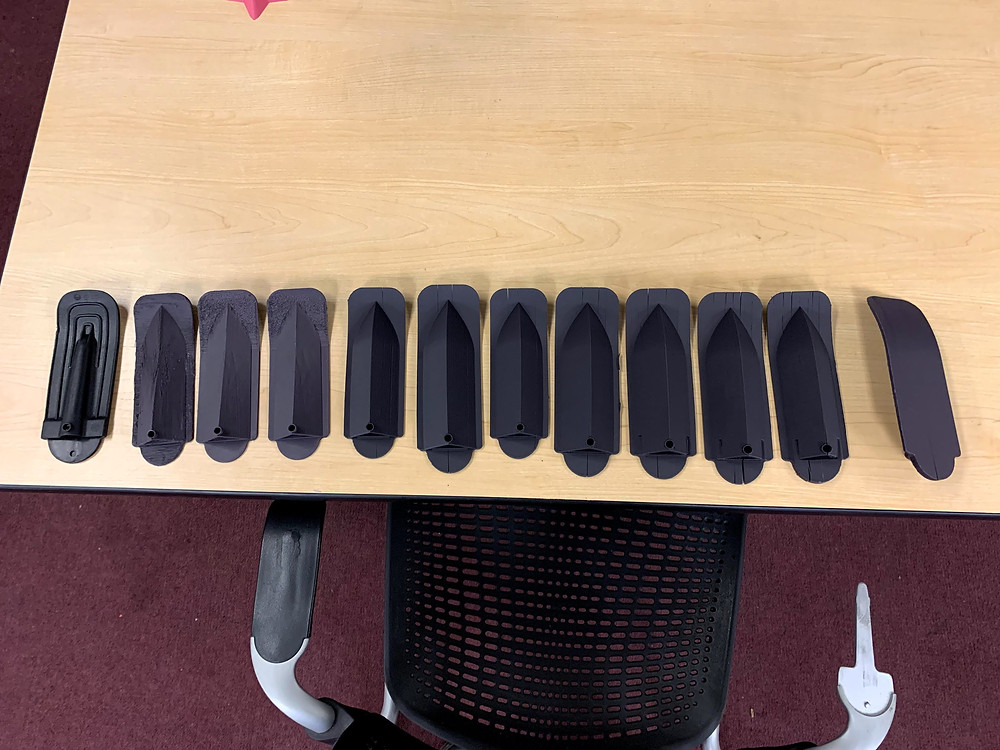 11 iterations of chair armrest lined up on a table with the original model on the far left
