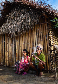 An elderly Temiar Orang Asli couple sits and enjoys the evening in front of their home located on a hill, surrounded by tapioca plants and an assortment of vegetables and fruit trees with a clean and clear river running close by.  In 2015, after over 30 years living in a government resettlement scheme, this couple were one of the first to return back to their traditional land after decades of waiting for a better life promised at resettlement village. Not long after moving back, more families, young and old, followed suit. Despite having no amenities and having to build everything from scratch, they attest that they are happier here now that they have autonomy, clean water and land to plant food.