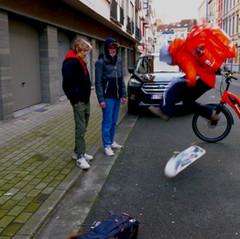 Een takeawayboy ziet zijn leeftijdgenoten een beetje sukkelen.   Hij stopt. Stapt van zijn fiets en toont een paar keren hoe het moet.   Daarna rijdt hij verder.