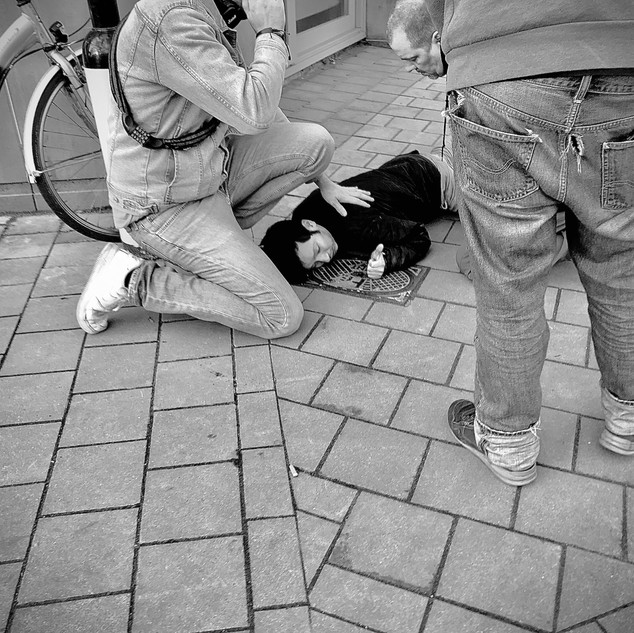 The man on the ground fell from his balcony while trying to enter his appartement.   As he was drunk, he shut his front door and forgot his key.  Fortunately he was not harmed and these concerned people helped him on his feet again.  Still drunk, he leaned against the wall just as the police arrived.  They first asked us what happened.   The first thing they asked him was to show his papers.