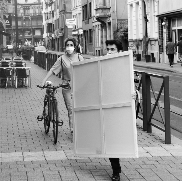 She takes care of his bike.  He carries the canvas for his or her opus to come.  Sleepstraat, Gent, on my way home.