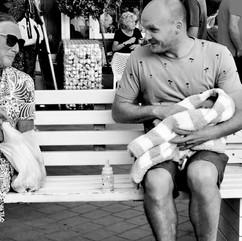 De vader geeft baby net het flesje gegeven.  Wat voor de man normaal lijkt vertedert de vrouw op de bank.   Deze generatie vaders doet het anders dan in haar tijd.