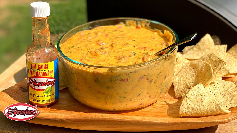 Cheesy smoked queso dip in a clear bowl, sitting beside a bottle of El Yucateco Hot Sauce and some tortilla chips for dipping. A great tailgating appetizer.