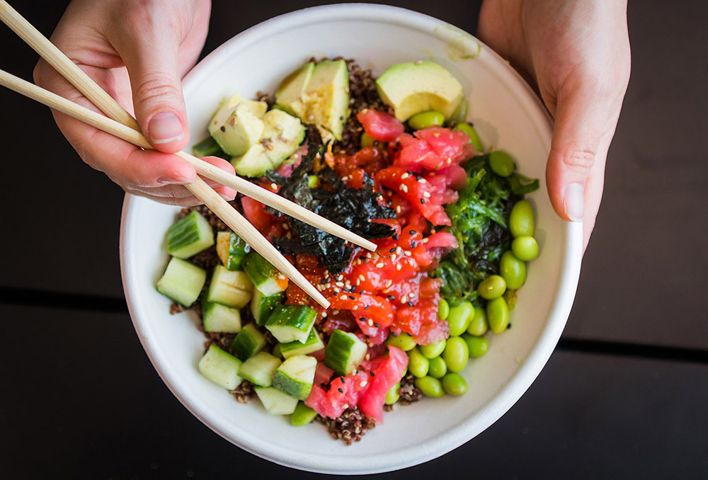 Poke bowl viewed from above with tuna, edamame, cucumber, avocado, and seaweed, with hand holding chopsticks.
