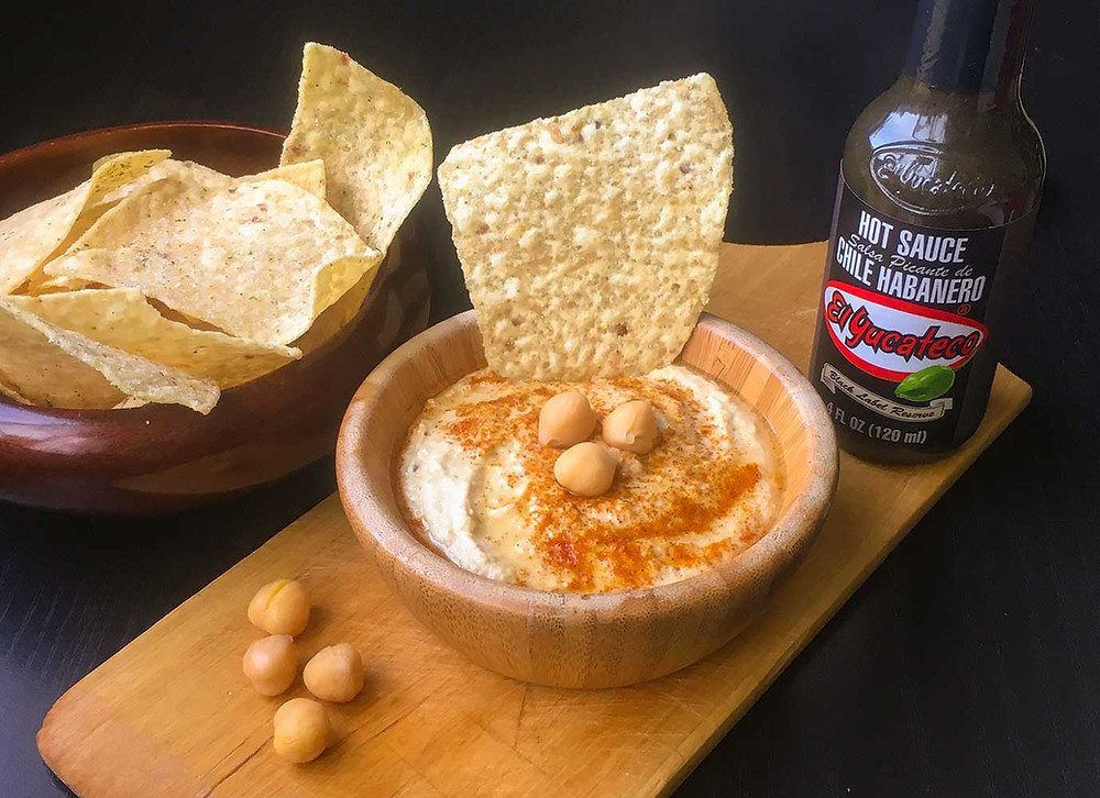 Bowl of fresh spicy hummus as an appetizer, beside a bowl of tortilla chips and bottle of El Yucateco authentic Mexican hot sauce