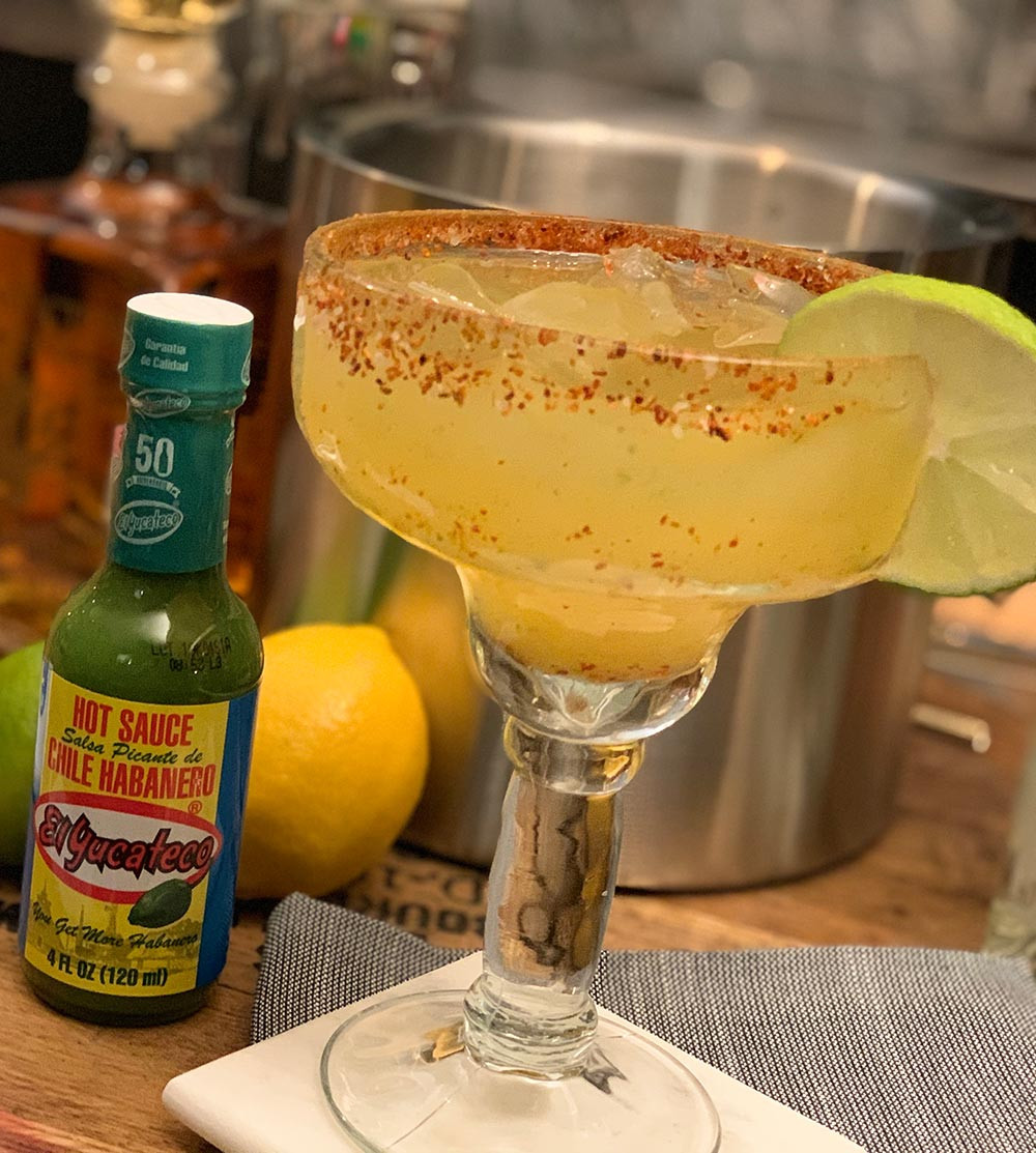 Green Devil Margarita with a lime garnish, featuring a bottle of El Yucateco Green Habanero Sauce. One of the best tailgating drinks!