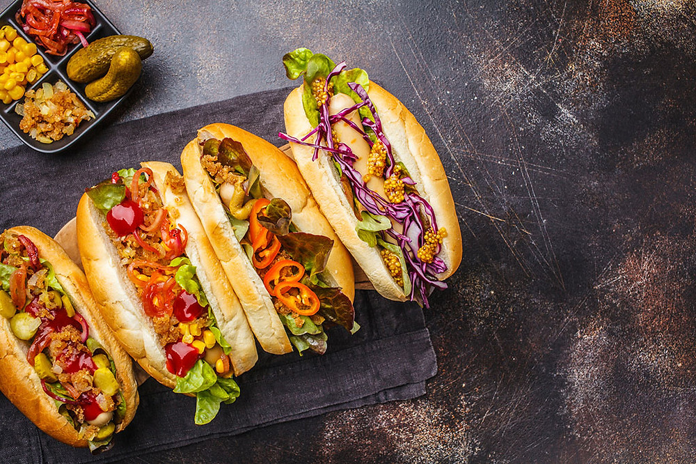 4 hot dogs lined up on a table with various brightly colored toppings.
