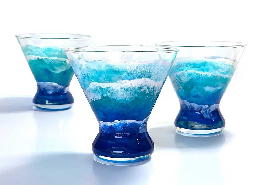 Trio of hand-painted Castaway Stemless Martini Glasses by Nelson Ruger, with tropical ocean waves washing up the clear glass