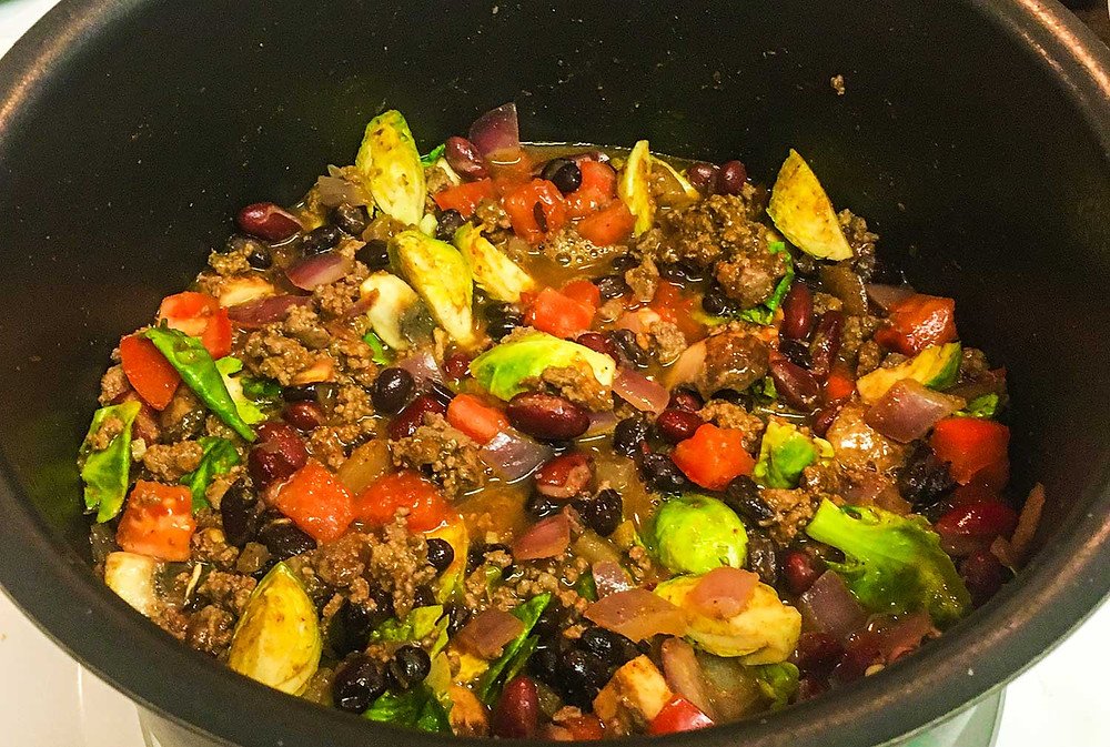Stock pot full of spicy chili featuring El Yucateco Hot Sauce and colorful fresh vegetables.
