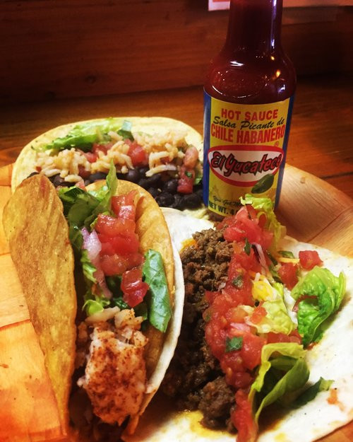 Beef soft taco and chicken hard taco with lettuce, tomato, and El Yucateco hot sauce from The Taco Spot, Charleston, South Carolina.