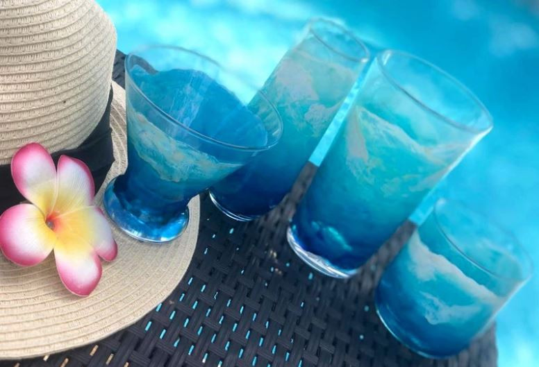 Set of 4 hand-painted cocktail glasses with blue and turquoise ocean waves, sitting by a pool and a hat with a pink flower