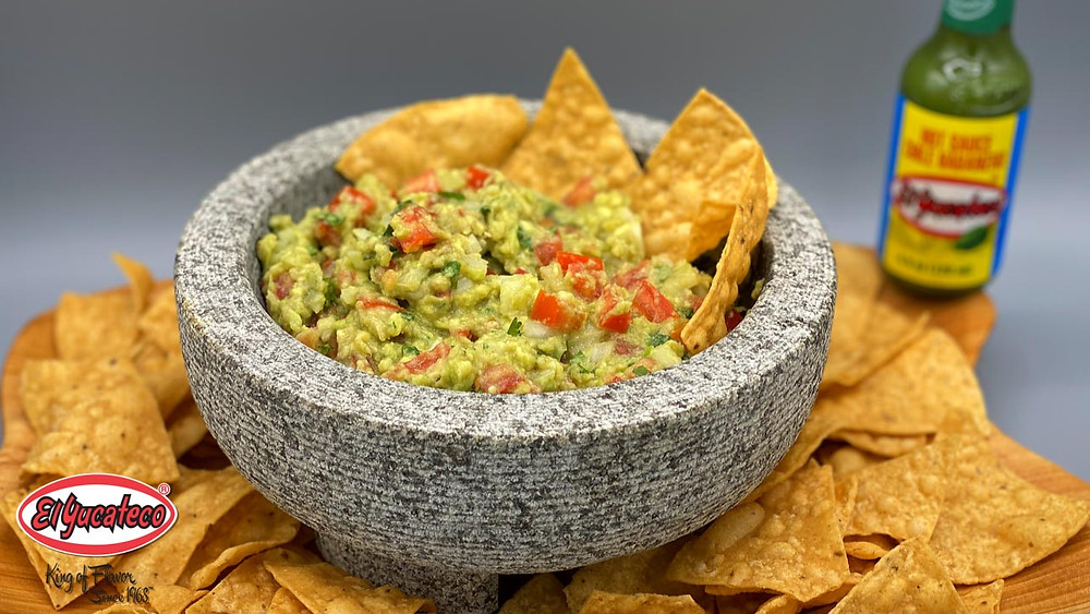 Bowl of fresh guacamole surrounded by tortilla chips and a bottle of El Yucateco Green Habanero Sauce, as part of tailgating menu.