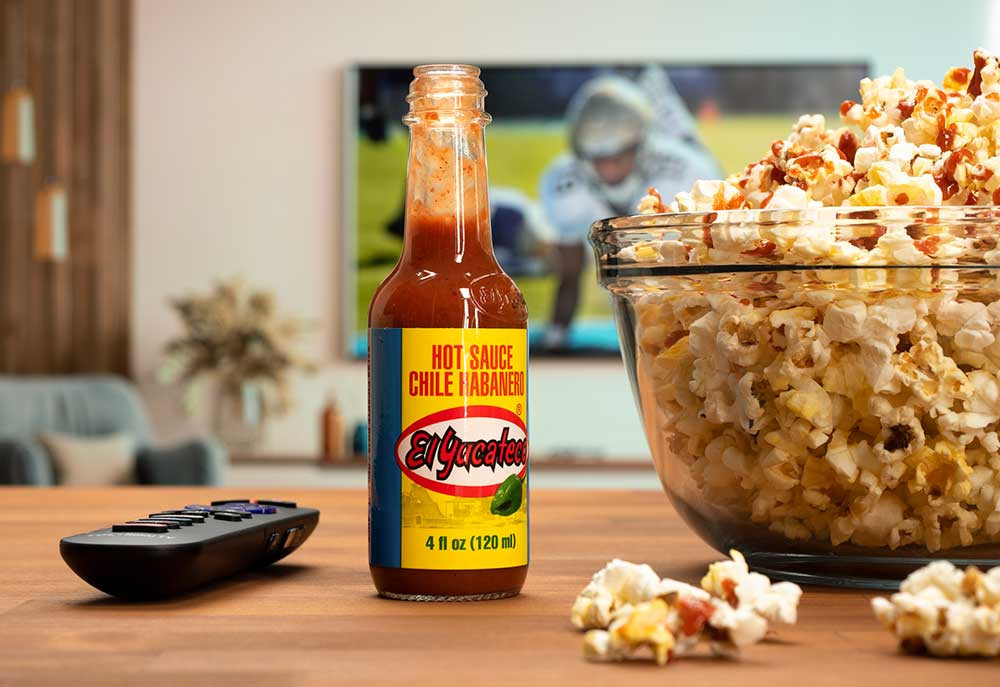 Bottle of El Yucateco Habanero Red Sauce next to a TV remote and a full bowl of fresh popcorn topped with hot sauce