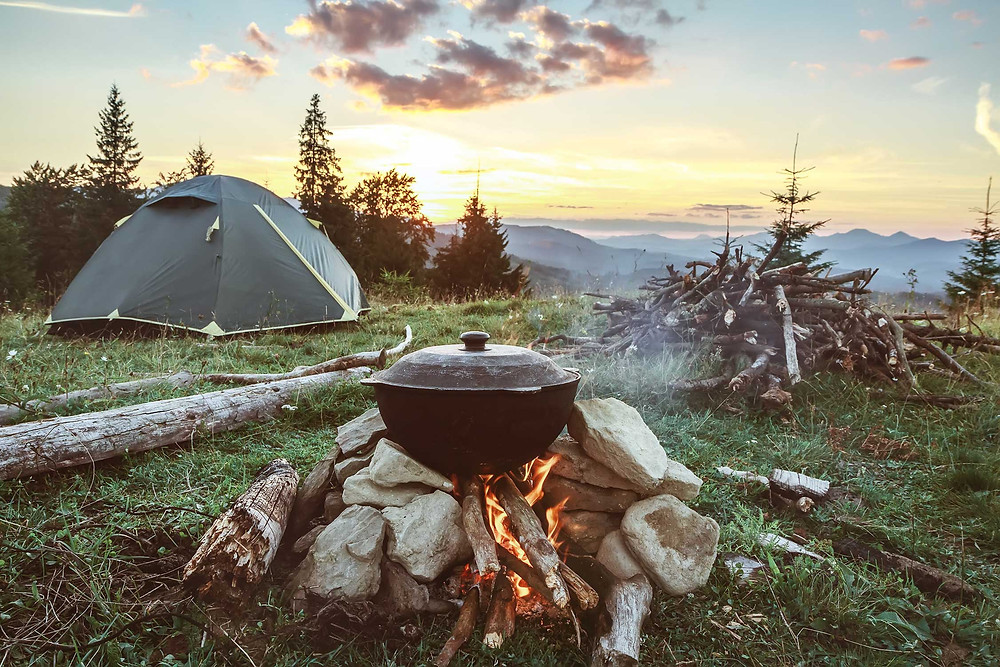 Campsite with large dutch oven cooking in a campfire, with tent and sun setting over mountains in the background