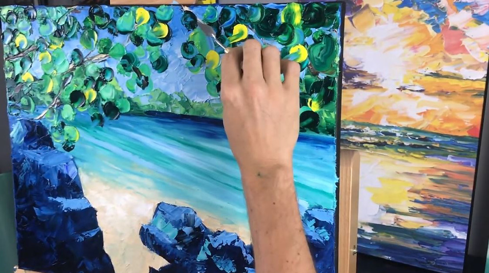 Nelson's hand holding a palette knife while painting Day Dreaming 2 with blue, green, and white oil paint.