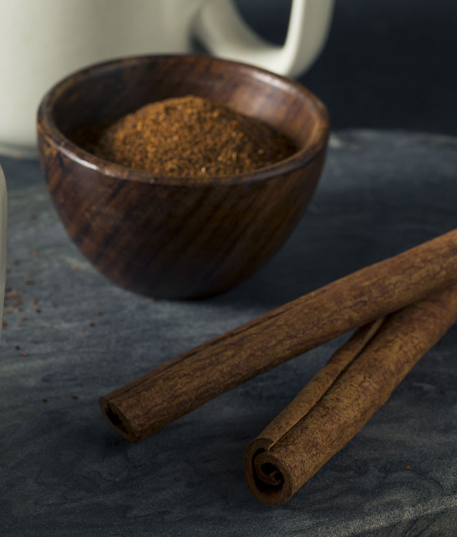 Ground cinnamon in a dark wood bowl and cinnamon sticks arranged on a kitchen surface. Ready to be used in a recipe for Mexican hot cocoa.