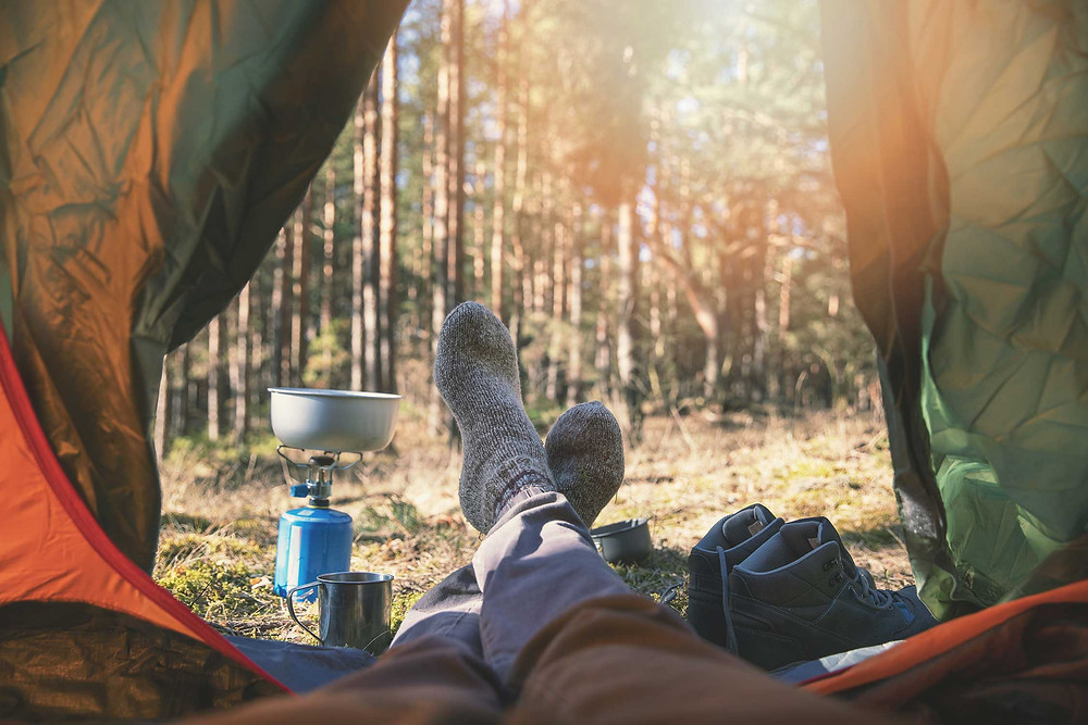 Man in tent, looking past his feet in gray socks at a forested campground viewed through the door of a camping tent.
